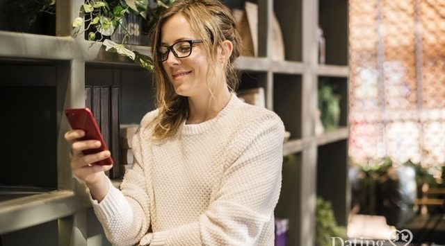 woman looking at dating profiles on her phone